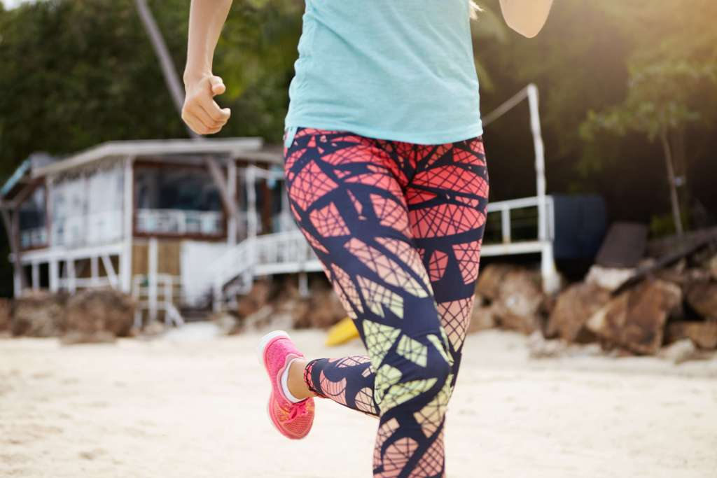 Women dressed in all over print legging running on the beach
