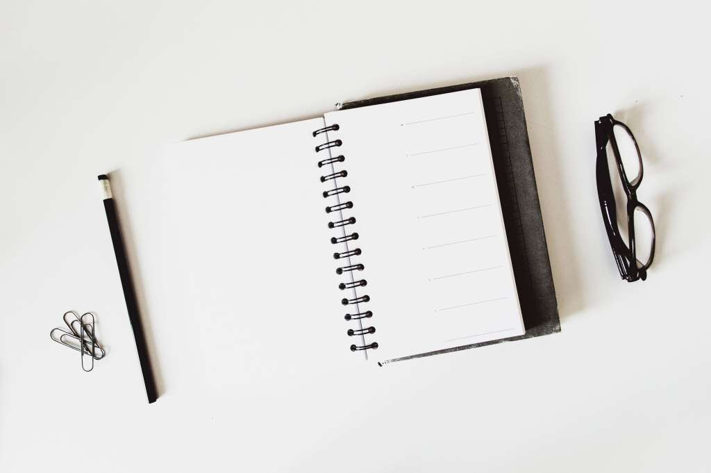 Empty planner with pen and glasses