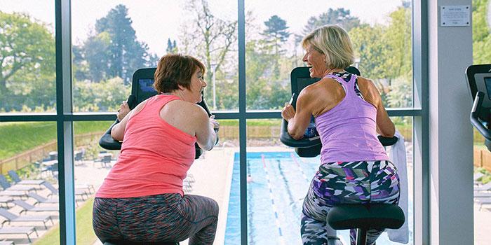 Ladies chatting on gym bike