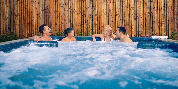 Friends relaxing in outdoor spa pool