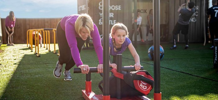 Image of a lady and a young girl pushing a sled on the Battlebox area