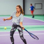 Image of a girl hitting a forehand on a carpet tennis court
