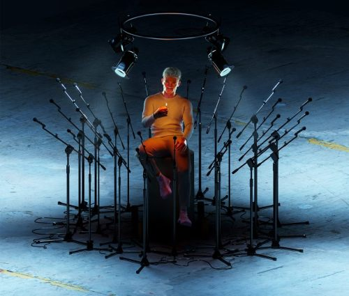 a render of a man alone in a room with microphones surrounding him