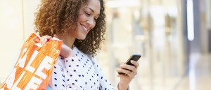 lady checks phone for text outside store holding phone