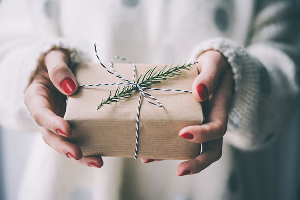 50646106 - woman's hands hold christmas or new year decorated gift box. toned picture