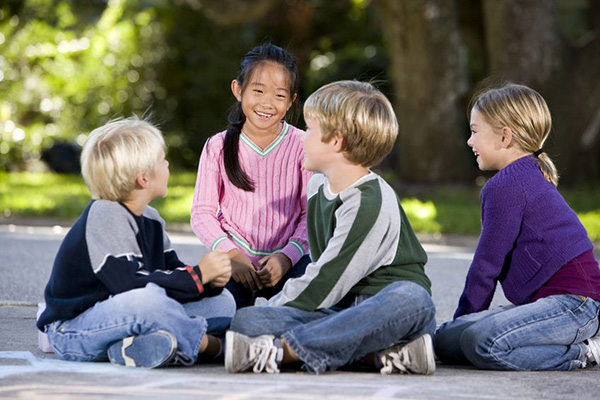 8167796 - four multi-ethnic children sitting together smiling outdoors, ages 7 to 9, focus on asian girl