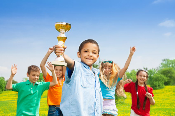 20981364 - portrait of black happy smiling little boy holding prize cup with his team on background