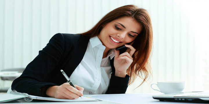 24194675-Young-happy-businesswoman-talking-on-the-phone-and-writing-notes-in-office-Stock-Photo