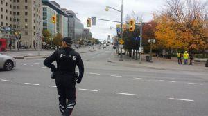 An armed officer walking toward the shooting scene