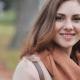 Mulher com roupas de inverno e no fundo um parque.
