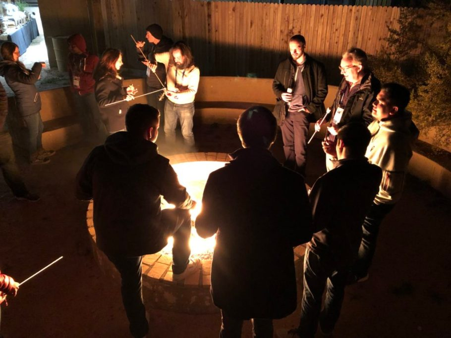 A group of developers huddles around a firepit with marshmallows on sticks