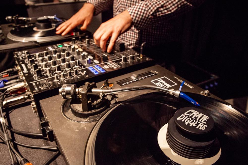 dj using a record weight to reduce sound wave vibrations impact on a vinyl record