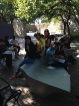 Students experiencing and talking about Zaha Hadid's bench outside in the DMA Sculpture Garden.
