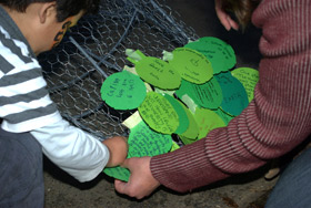 Children attach cardboard feathers to the giant kakapo.