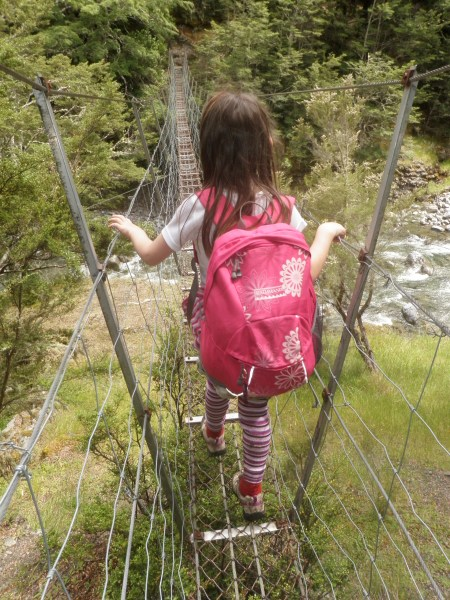 Meg crossing a river on a swingbridge; Photo: Steve Baker.