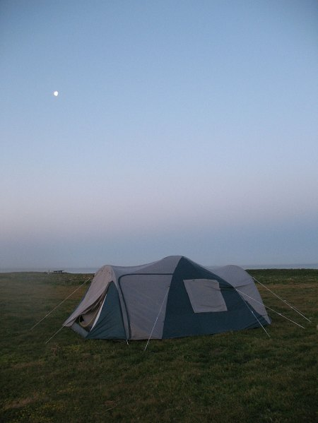 Camping. Our tent at dawn. Full moon in a clear sky.
