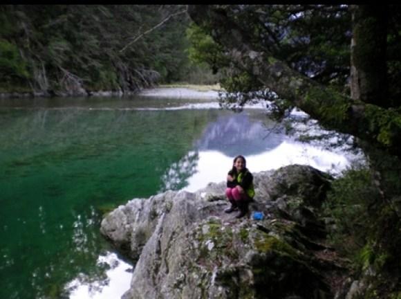 Jamie sitting on rocks by Lake Sylvan.