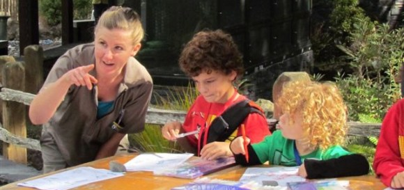 Ali helps children colour in whio images at Auckland Zoo.