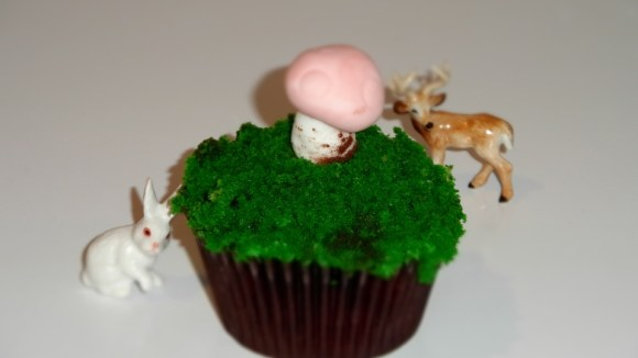A cupcake with grass, a mushroom and animals as decoration.