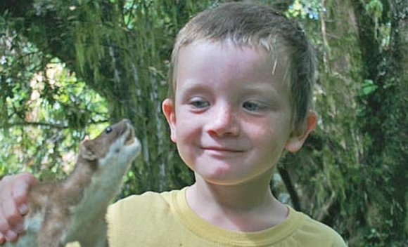 A student, 5 year old Asten, holds a stuffed stoat.