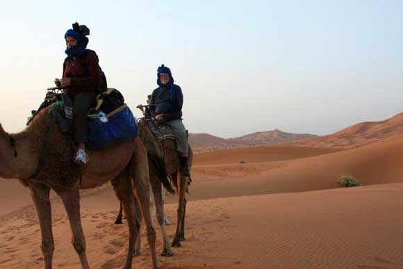 Ashley and Susan at dawn in the Sahara riding a camel after spending the night in a Bedouin tent.