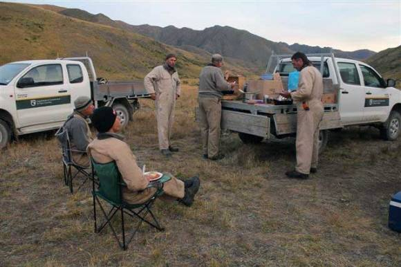 Five DOC workers sitting and standing around two DOC utes sharing some food.