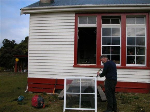 Greg outside Port Craig Hut preparing a window.