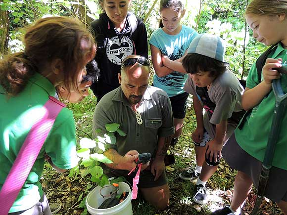 DOC Ranger, Joe Waikari, shows Te Karaka students how to GPS their trap location, so that when they come back to check the trap-line they can find the trap again.
