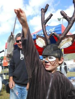 A rat being held by a boy in a deer costume.