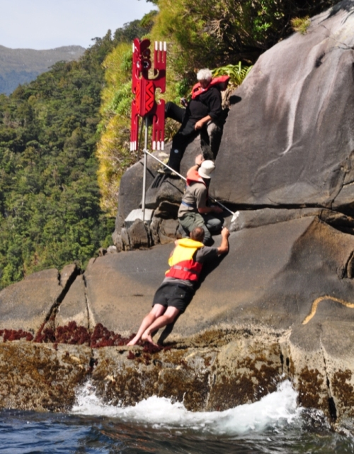 High winds and steep, slippery rocks make installing some of the poupou difficult. Here Pete Young braces Allan Harms so that he can use the drill, while Ronnie Bull (above) keeps the poupou straight.