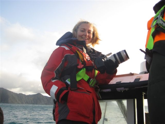 Nadine with her camera taking photos of humpback whales in Cook Strait.