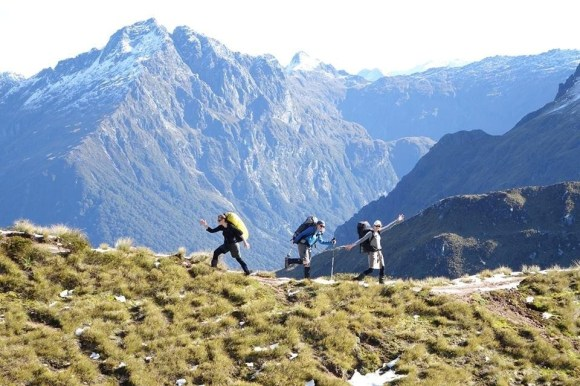 Susie and friends dancing on the Kepler Track with mountains in the background.