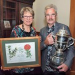 Clive Paton with his wife Phyll displaying the cup and artwork.