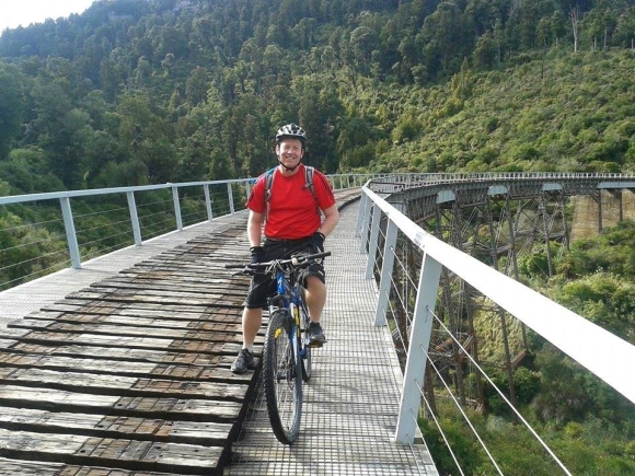 Andrew Mercer biking along a bridge on the Old Coach Road.