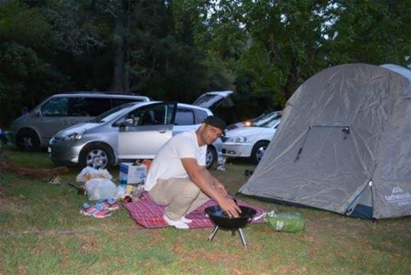 Abhishek setting up a camp stove while camping in Rotorua.