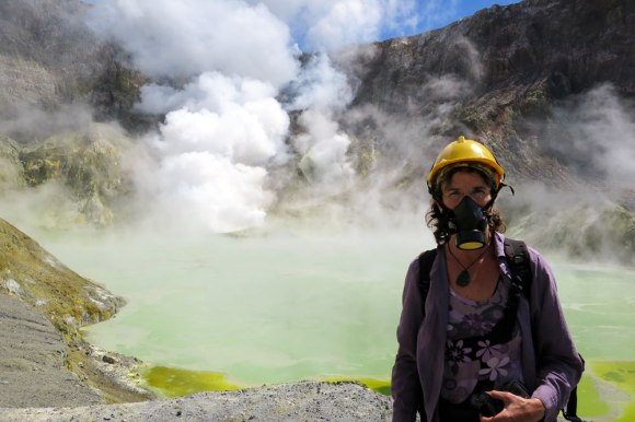 Sally, in a hard hat and face mask, standing in front of a steaming crater lake on White Island.