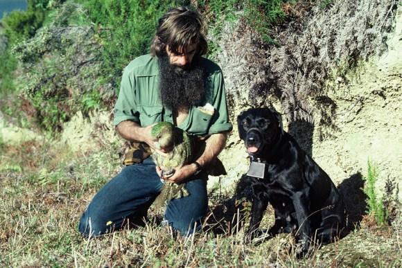 Gary Aburn holding a kākāpō with dog Mandy.