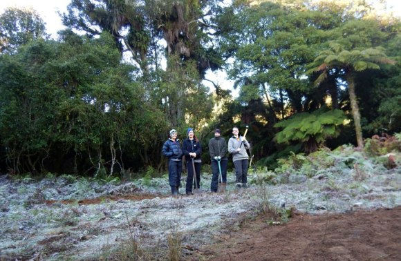 The four women standing on the site of the old huts.
