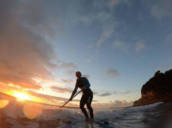 Catching a wave at sunrise in Long Bay-Okura.
