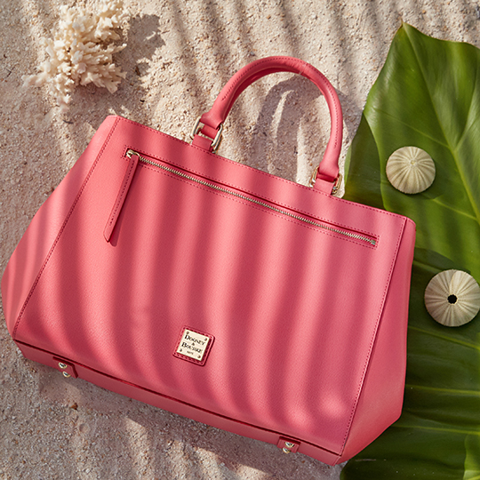 A Dooney & Bourke Saffiano satchel in Bubble Gum pink on sandy beach.