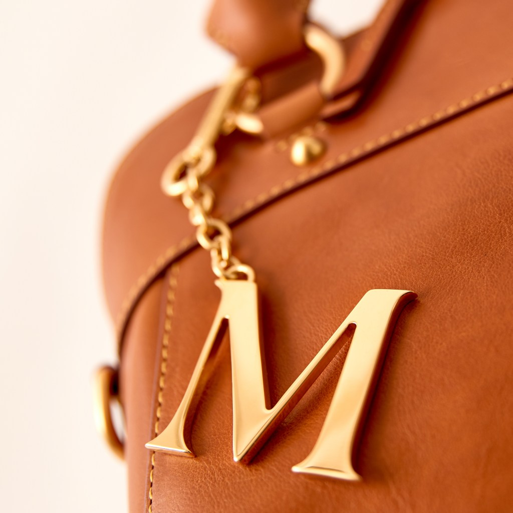 "An ""M"" monogram charm pendant coated in 24k gold fastened to a handbag."