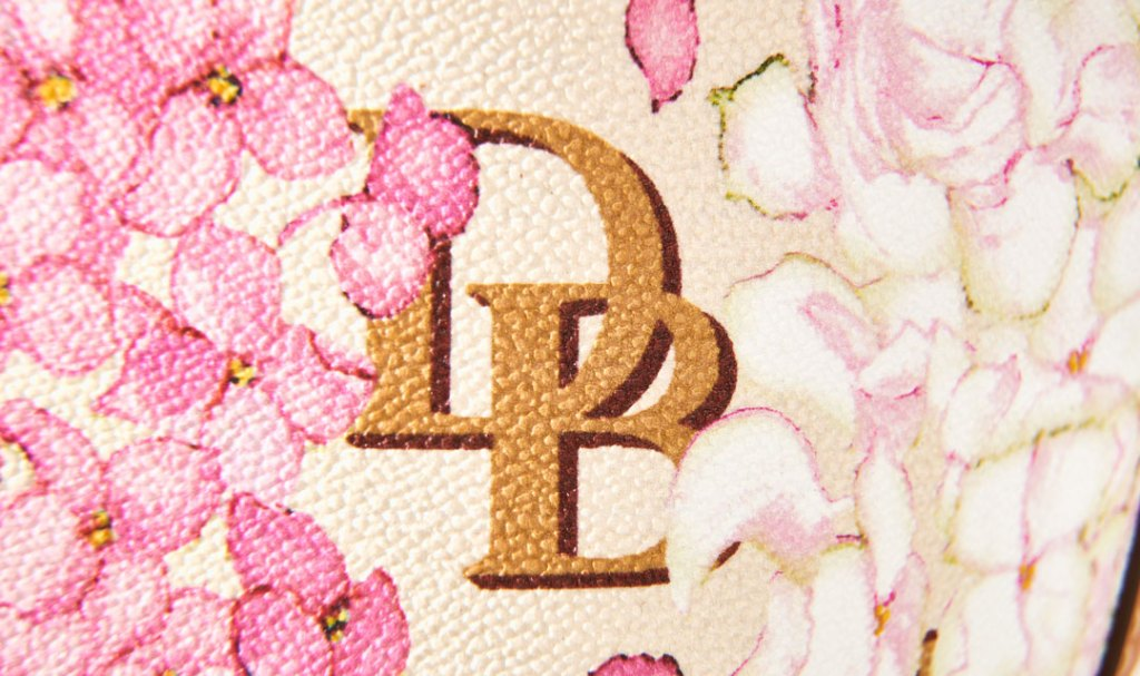 The D&B logo, surrounded by printed hydrangea flowers, on our new Hydrangra Monogram bag.