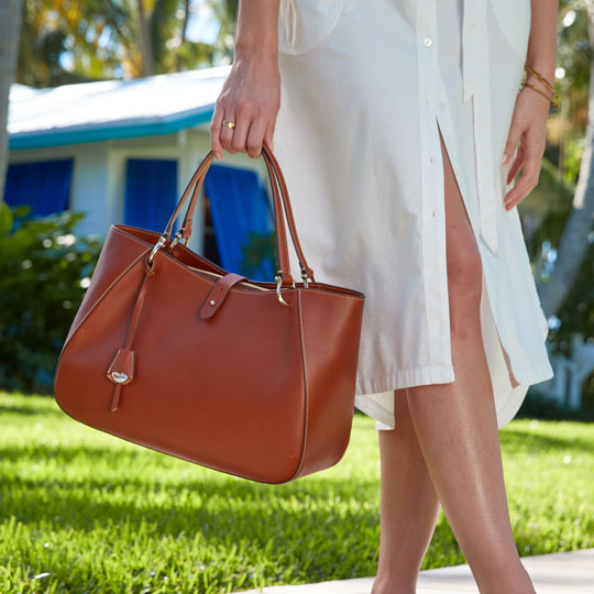 A woman carries the Camilla shoulder bag in saddle brown.