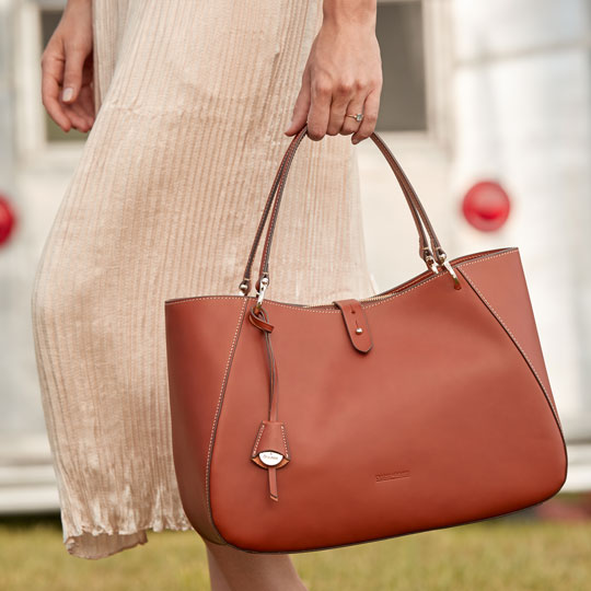 A woman holding the Camilla shoulder bag.