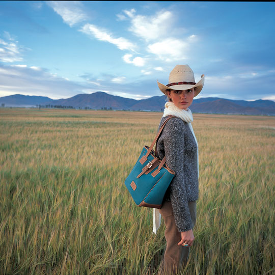 A woman stands in the fields outside of Jackson Hole, WY holding a blue shoulder bag.