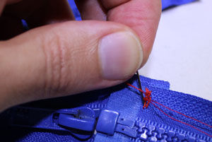 Stitch the overlap on one side of the zipper.