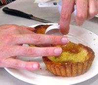 Hand touching a tart.