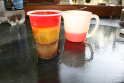 Plastic cup with three differently coloured, frozen layers.