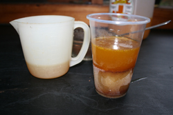 Plastic cup with a frozen layer on the bottom and a liquid layer on top.