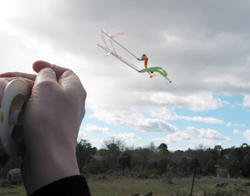 Hand holding the string of a kite as it flies in the air.